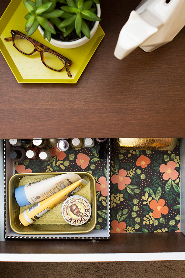 Don't skip your nightstand when spring cleaning! Line the drawer with pretty floral wrapping paper and use small bins spray painted gold to organize often used items