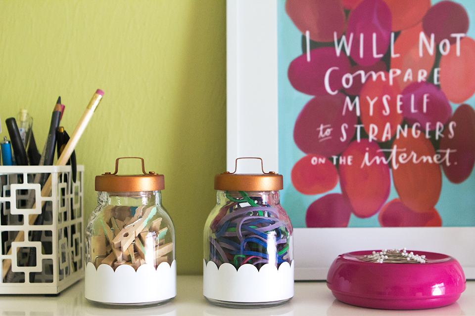 Dress up your desk with these cute DIY scalloped storage containers. The trick is white adhesive vinyl and rose gold spray paint.