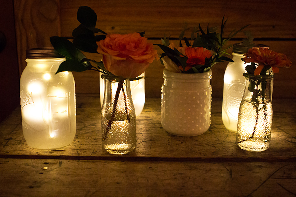 Love the mix of frosted LED mason jar lights and vintage vases at this rustic wedding.