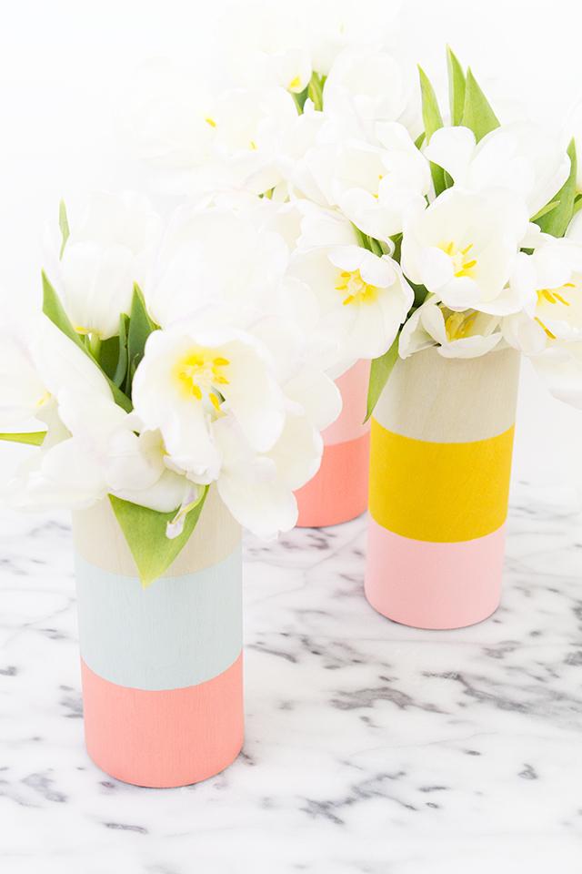 Wrap pain cylinder vases in adhesive wood veneer to create these gorgeous, modern vases!