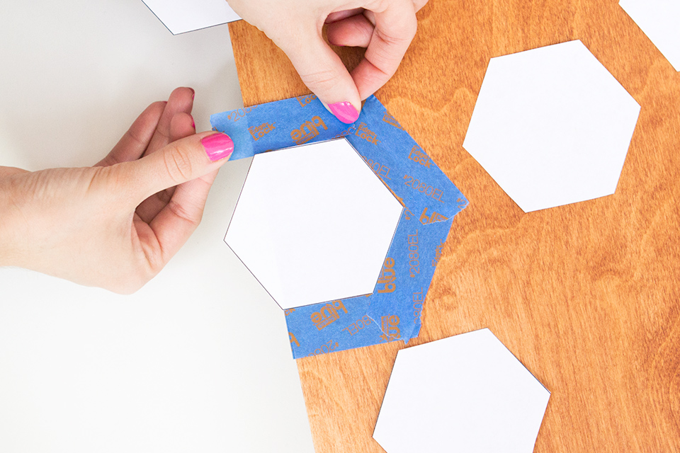 Apply painters tape around paper hexagons to create stencils for a beautiful, modern wall art piece.