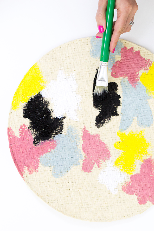 Use a larger paint brush to transform ready-made woven straw placemats into bold floral ones inspired by the Kate Spade Saturday collection.