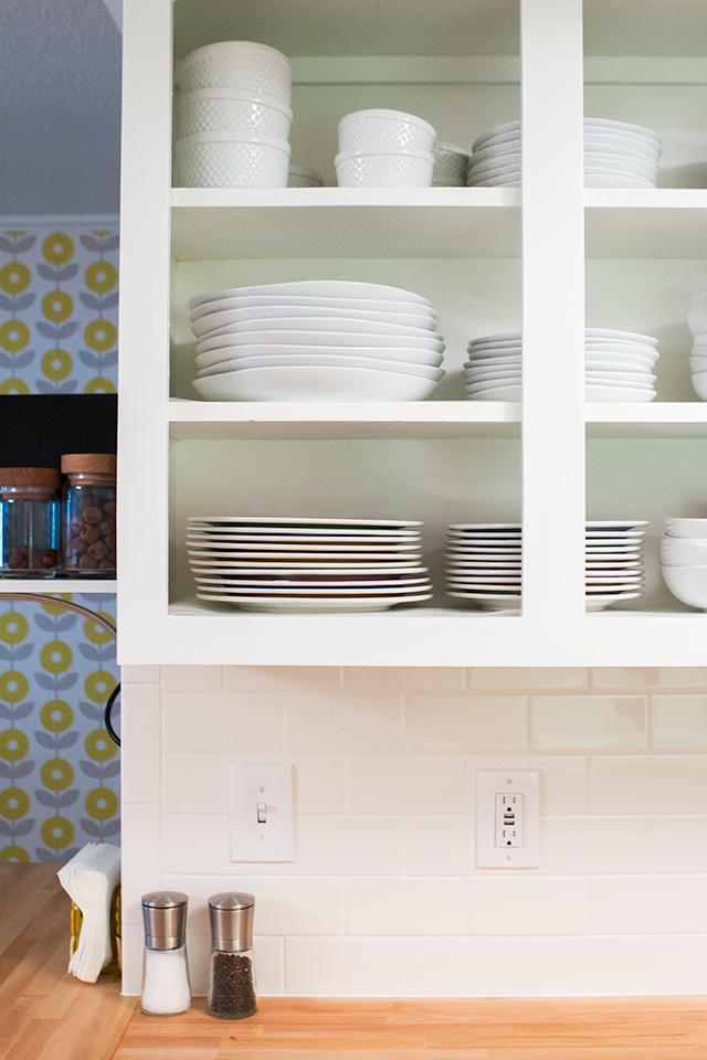 Convert your existing cabinets into open shelving by removing the doors, filling the hardware holes, and painting it bright white.